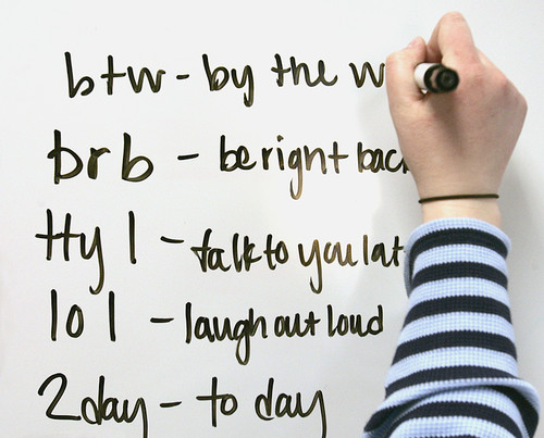 whiteboard with commonly used texting abbreviation examples
